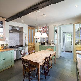 ロンドンのシャビーシック調のおしゃれなキッチン (エプロンフロントシンク、シェーカースタイル扉のキャビネット、緑のキャビネット、白いキッチンパネル、サブウェイタイルのキッチンパネル、シルバーの調理設備の) の写真