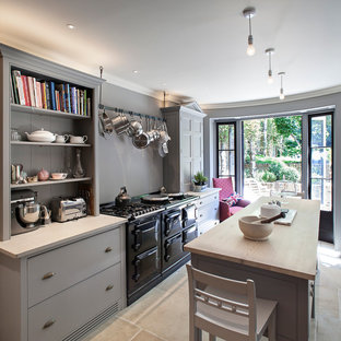 Photo of a medium sized traditional l-shaped enclosed kitchen in London with grey cabinets, grey splashback, ceramic splashback and an island.