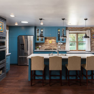 Transitional kitchen appliance - Transitional u-shaped dark wood floor and brown floor kitchen photo in Other with a drop-in sink, shaker cabinets, blue cabinets, red backsplash, brick backsplash, stainless steel appliances, an island and white countertops