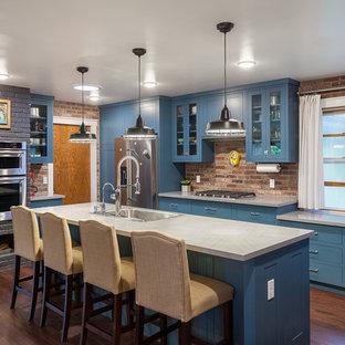 他の地域のトランジショナルスタイルのおしゃれなキッチン (青いキャビネット、人工大理石カウンター、レンガのキッチンパネル、シルバーの調理設備の、濃色無垢フローリング、茶色い床、シングルシンク、ガラス扉のキャビネット) の写真