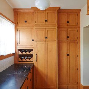 Geräumige Mid-Century Küche mit Landhausspüle, Kassettenfronten, hellbraunen Holzschränken, Granit-Arbeitsplatte, Küchenrückwand in Schwarz, Keramikboden, buntem Boden und schwarzer Arbeitsplatte in Sonstige