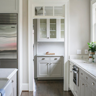 Photo of an arts and crafts open plan kitchen in Atlanta with a farmhouse sink, glass-front cabinets, white cabinets, white splashback, ceramic splashback, stainless steel appliances, dark hardwood floors and with island.