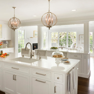 Example of a large classic medium tone wood floor open concept kitchen design in Minneapolis with an undermount sink, shaker cabinets, white cabinets, two islands and white countertops