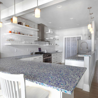 This is an example of a mid-sized beach style galley open plan kitchen in Charleston with white cabinets, a peninsula, recycled glass benchtops, white splashback, medium hardwood floors, a double-bowl sink, flat-panel cabinets, subway tile splashback, stainless steel appliances and beige floor.