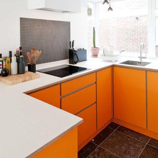 Modern inredning av ett avskilt, litet u-kök, med släta luckor, orange skåp, grått stänkskydd, stänkskydd i mosaik och svart golv