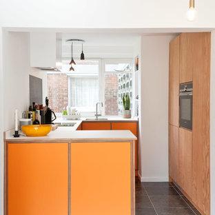Idée de décoration pour une petit cuisine design en U fermée avec un évier encastré, un placard à porte plane, des portes de placard oranges, un plan de travail en stratifié, une crédence grise, un électroménager en acier inoxydable, un sol noir et aucun îlot.
