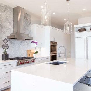 バンクーバーの大きいエクレクティックスタイルのおしゃれなキッチン (ドロップインシンク、フラットパネル扉のキャビネット、白いキャビネット、御影石カウンター、白いキッチンパネル、磁器タイルのキッチンパネル、シルバーの調理設備の、無垢フローリング、茶色い床、白いキッチンカウンター) の写真