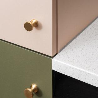 На фото: маленькая угловая кухня-гостиная в современном стиле с одинарной раковиной, розовой кухней, столешницей из акрилового камня, белым фартуком, светлым паркетным полом, коричневым полом и белой столешницей с