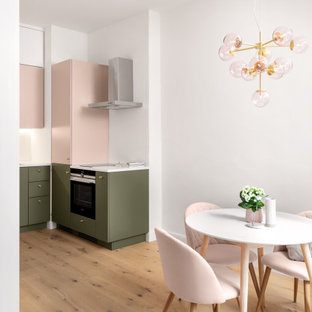 Small contemporary l-shaped open plan kitchen in Munich with a single-bowl sink, pink cabinets, solid surface benchtops, white splashback, light hardwood floors, brown floor and white benchtop.