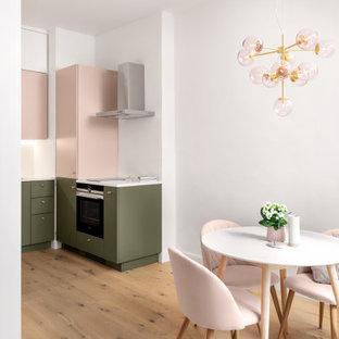 Modelo de cocina en L, contemporánea, pequeña, abierta, con fregadero de un seno, encimera de acrílico, salpicadero blanco, suelo de madera clara, suelo marrón y encimeras blancas