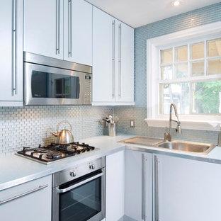 Idéer för att renovera ett litet funkis l-kök, med en nedsänkt diskho, släta luckor, vita skåp, blått stänkskydd, stänkskydd i metallkakel, rostfria vitvaror och svart golv