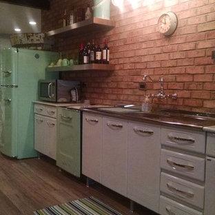ワシントンD.C.の中サイズのエクレクティックスタイルのおしゃれなキッチン (一体型シンク、フラットパネル扉のキャビネット、白いキャビネット、人工大理石カウンター、茶色いキッチンパネル、レンガのキッチンパネル、カラー調理設備、無垢フローリング、茶色い床、アイランドなし) の写真
