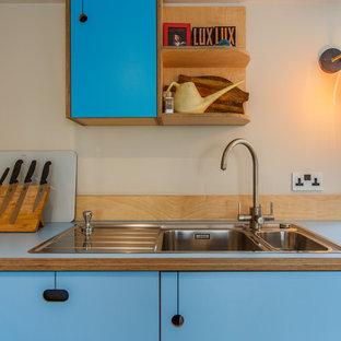 Идея дизайна: угловая кухня среднего размера в стиле фьюжн с обеденным столом, плоскими фасадами, бирюзовыми фасадами, столешницей из ламината, полуостровом и синей столешницей
