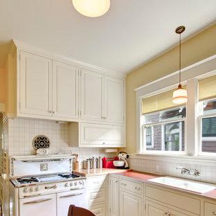 Klassische Wohnküche mit Einbauwaschbecken, weißen Elektrogeräten, Laminat-Arbeitsplatte, weißen Schränken, Küchenrückwand in Weiß, profilierten Schrankfronten, buntem Boden und roter Arbeitsplatte in Portland