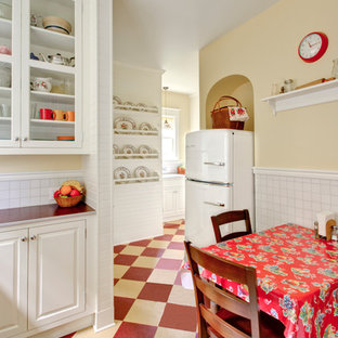 Идея дизайна: кухня в классическом стиле с обеденным столом, фасадами с выступающей филенкой, белыми фасадами, столешницей из ламината, белым фартуком, белой техникой, разноцветным полом и красной столешницей