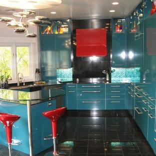 デンバーの中くらいのエクレクティックスタイルのおしゃれなキッチン (アンダーカウンターシンク、フラットパネル扉のキャビネット、青いキャビネット、ガラスカウンター、青いキッチンパネル、ガラス板のキッチンパネル、シルバーの調理設備、リノリウムの床) の写真