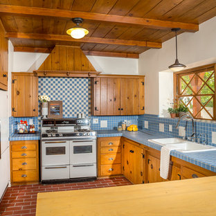 Inspiration for a mid-sized traditional l-shaped kitchen in Los Angeles with a drop-in sink, medium wood cabinets, tile benchtops, white appliances, shaker cabinets, blue splashback, porcelain splashback, brick floors and blue benchtop.