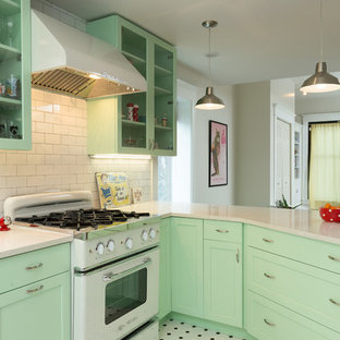 Inspiration for a medium sized traditional l-shaped open plan kitchen in Chicago with shaker cabinets, green cabinets, white splashback, metro tiled splashback, white appliances, a breakfast bar, a belfast sink, engineered stone countertops and porcelain flooring.