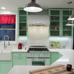 Photo of a mid-sized traditional l-shaped open plan kitchen in Chicago with a farmhouse sink, shaker cabinets, green cabinets, quartz benchtops, white splashback, subway tile splashback, white appliances, a peninsula and porcelain floors.