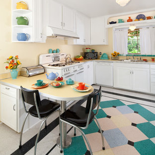 Mid-sized midcentury u-shaped kitchen in Santa Barbara with white cabinets, laminate benchtops, white appliances, shaker cabinets, linoleum floors, a double-bowl sink, with island, multi-coloured floor and white benchtop.