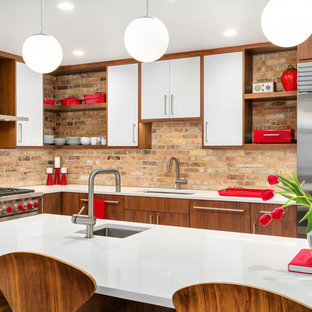Photo of a midcentury l-shaped kitchen in Chicago with an undermount sink, flat-panel cabinets, dark wood cabinets, brown splashback, brick splashback, stainless steel appliances, with island, white benchtop and quartz benchtops.