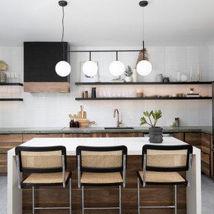 Moderne Küche in L-Form mit Unterbauwaschbecken, flächenbündigen Schrankfronten, hellbraunen Holzschränken, Küchengeräten aus Edelstahl, Kücheninsel, grauem Boden und grüner Arbeitsplatte in Phoenix