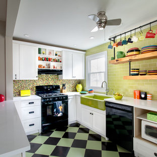 Example of a mid-sized cottage u-shaped ceramic floor and multicolored floor kitchen design in Philadelphia with a farmhouse sink, shaker cabinets, white cabinets, quartz countertops, green backsplash, subway tile backsplash, black appliances and a peninsula