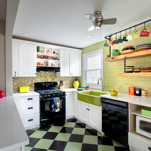 Photo of a mid-sized country u-shaped kitchen in Philadelphia with a farmhouse sink, shaker cabinets, white cabinets, quartz benchtops, green splashback, subway tile splashback, black appliances, ceramic floors, a peninsula and multi-coloured floor.