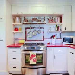 チャールストンの小さいエクレクティックスタイルのおしゃれなキッチン (アンダーカウンターシンク、シェーカースタイル扉のキャビネット、白いキャビネット、クオーツストーンカウンター、白いキッチンパネル、サブウェイタイルのキッチンパネル、シルバーの調理設備の、セラミックタイルの床) の写真
