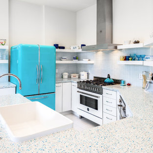 Photo of a small eclectic u-shaped eat-in kitchen in San Francisco with a farmhouse sink, flat-panel cabinets, white cabinets, recycled glass benchtops, blue splashback, glass sheet splashback and porcelain floors.