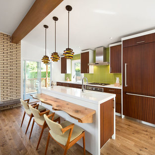 Photo of a midcentury galley open plan kitchen in Vancouver with an undermount sink, quartz benchtops, green splashback, panelled appliances, flat-panel cabinets, medium hardwood floors, with island and medium wood cabinets.