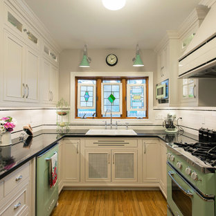 This is an example of a small midcentury u-shaped separate kitchen in Boston with a double-bowl sink, recessed-panel cabinets, white cabinets, granite benchtops, white splashback, coloured appliances, medium hardwood floors, no island, ceramic splashback and brown floor.