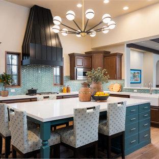 Große Mid-Century Wohnküche in U-Form mit Landhausspüle, profilierten Schrankfronten, braunen Schränken, Quarzwerkstein-Arbeitsplatte, Küchenrückwand in Blau, Rückwand aus Porzellanfliesen, Küchengeräten aus Edelstahl, braunem Holzboden, Kücheninsel, braunem Boden und weißer Arbeitsplatte in Phoenix