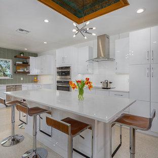 Ejemplo de cocina de galera, retro, de tamaño medio, cerrada, con fregadero bajoencimera, armarios con paneles lisos, puertas de armario blancas, encimera de cuarzo compacto, salpicadero gris, salpicadero de azulejos de vidrio, electrodomésticos de acero inoxidable, suelo de terrazo, una isla, suelo beige y encimeras blancas