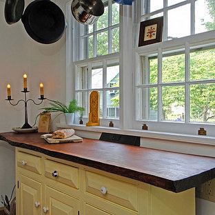 Design ideas for a small eclectic u-shaped separate kitchen in Philadelphia with a farmhouse sink, raised-panel cabinets, yellow cabinets, terra-cotta splashback, white appliances, slate floors, no island, wood benchtops and beige splashback.