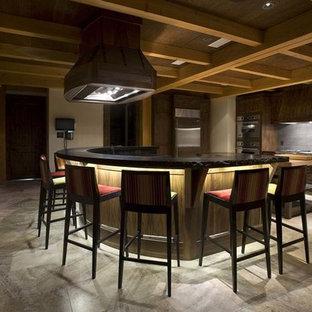 バンクーバーの巨大なラスティックスタイルのおしゃれなキッチン (エプロンフロントシンク、シェーカースタイル扉のキャビネット、濃色木目調キャビネット、御影石カウンター、グレーのキッチンパネル、セラミックタイルのキッチンパネル、シルバーの調理設備の、トラバーチンの床) の写真