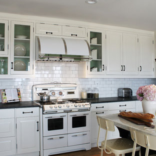 Mid-sized transitional eat-in kitchen ideas - Inspiration for a mid-sized transitional u-shaped medium tone wood floor eat-in kitchen remodel in Los Angeles with a farmhouse sink, white cabinets, marble countertops, white backsplash, subway tile backsplash, stainless steel appliances, an island and raised-panel cabinets