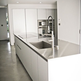 Inspiration for a large midcentury galley separate kitchen in Los Angeles with an integrated sink, flat-panel cabinets, white cabinets, stainless steel benchtops, stainless steel appliances, concrete floors, with island and grey floor.
