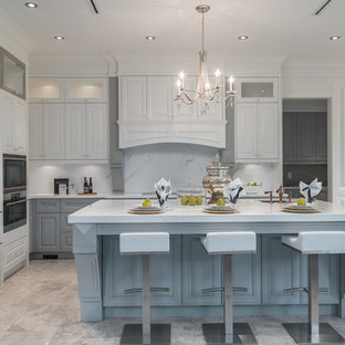 Design ideas for a large traditional l-shaped open plan kitchen in Vancouver with an undermount sink, raised-panel cabinets, white cabinets, solid surface benchtops, white splashback, marble splashback, stainless steel appliances, marble floors and with island.