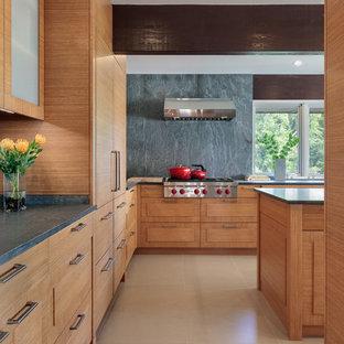 Foto di una grande cucina minimal con lavello sottopiano, ante con bugna sagomata, ante in legno scuro, top in pietra calcarea, paraspruzzi grigio, paraspruzzi in lastra di pietra, elettrodomestici da incasso, pavimento in gres porcellanato, isola e pavimento beige