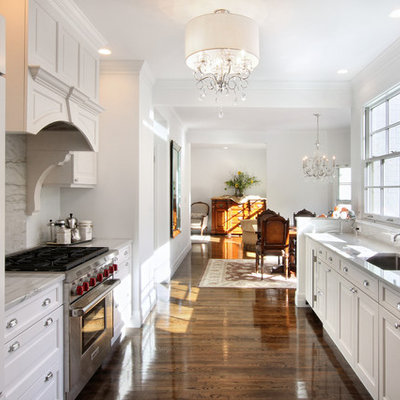 Example of a classic galley medium tone wood floor eat-in kitchen design in New York with an undermount sink, recessed-panel cabinets, white cabinets, marble countertops, gray backsplash, paneled appliances and marble backsplash
