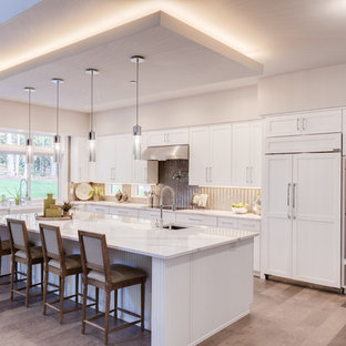 Mid-sized contemporary open concept kitchen ideas - Mid-sized trendy l-shaped light wood floor and beige floor open concept kitchen photo in Seattle with a farmhouse sink, shaker cabinets, white cabinets, quartz countertops, metallic backsplash, paneled appliances, an island and white countertops