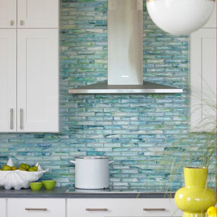 Beach style eat-in kitchen in Boston with shaker cabinets, white cabinets, glass tile splashback, granite benchtops, blue splashback, stainless steel appliances and with island.