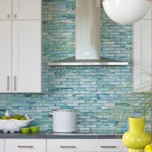 Exempel på ett maritimt kök och matrum, med skåp i shakerstil, vita skåp, stänkskydd i glaskakel, granitbänkskiva, blått stänkskydd, rostfria vitvaror och en köksö
