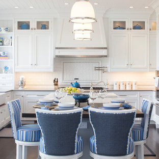 Eat-in kitchen - large traditional u-shaped dark wood floor eat-in kitchen idea in New York with a farmhouse sink, white cabinets, white backsplash, subway tile backsplash, stainless steel appliances, an island and shaker cabinets