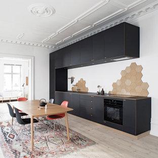 Foto de cocina comedor lineal, nórdica, grande, sin isla, con armarios con paneles lisos, puertas de armario negras, salpicadero beige, electrodomésticos negros, suelo de madera clara, fregadero encastrado y encimera de madera