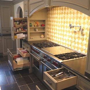 Immagine di una grande cucina tradizionale con lavello sottopiano, ante con riquadro incassato, ante beige, top in rame, paraspruzzi giallo, paraspruzzi con piastrelle di vetro, elettrodomestici in acciaio inossidabile, pavimento in ardesia e isola