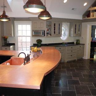 Ispirazione per una grande cucina chic con lavello sottopiano, ante con riquadro incassato, ante beige, top in rame, paraspruzzi giallo, paraspruzzi con piastrelle di vetro, elettrodomestici in acciaio inossidabile, pavimento in ardesia e isola