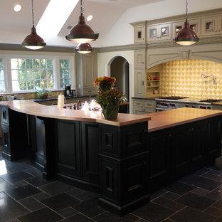 Immagine di una grande cucina chic con top in rame, lavello sottopiano, pavimento in ardesia, elettrodomestici in acciaio inossidabile, ante con riquadro incassato, ante beige, paraspruzzi giallo, paraspruzzi con piastrelle di vetro e isola