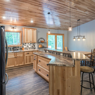 Inspiration for a medium sized rustic l-shaped kitchen/diner in Minneapolis with a built-in sink, shaker cabinets, light wood cabinets, granite worktops, multi-coloured splashback, glass tiled splashback, stainless steel appliances, vinyl flooring, an island, brown floors and multicoloured worktops.